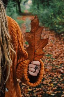 Фото Девушка держит в руке осенний дубовый листок