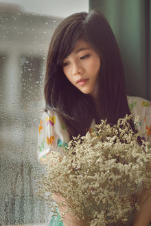 Фото Девушка азиатской внешности с букетом цветов у окна