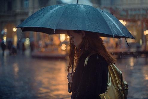 Фото Девушка под зонтом идет по улице города