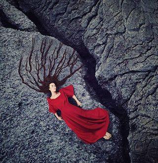 Фото Девушка в красном платье, с длинными волосами лежит на земле. Фотограф художник Килли Спэрри / Kylli Sparre