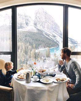 Фото Отец завтракает с сыном у большого окна из которого открывается потрясающий горный пейзаж