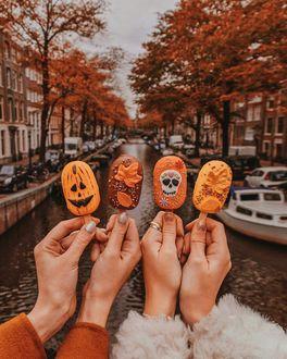 Фото Женские руки с мороженным, выполненным в осеннем стиле, на фоне городской улицы