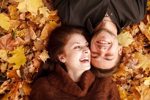 Фото Влюбленная счастливая пара лежит на осенней листве