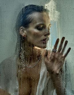 Фото Модель Edita Vilkeviciute стоит за стеклом в каплях от дождя