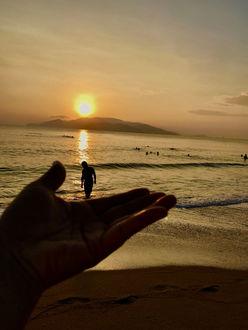 Фото Человек держит руку на фоне моря с мужчиной и купающимися людьми