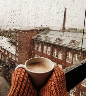 Фото В руках девушки чашка кофе на фоне города с дождем, by annasofiapark