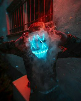 Фото Парень держит в руках светящуюся маску, от которой идет дым