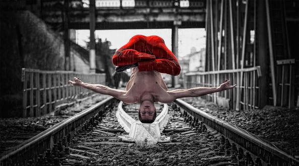 Фото Мужчина висит головой вниз, находясь в позе Лотоса, над железнодорожным полотном под дождем, фотограф Баженов Денис