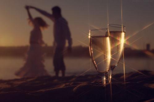 Фото Парень с девушкой в танце на берегу, на переднем плане два бокала с шампанским. Фотограф Алексей Доберман