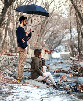 Фото Парень держит зонт над девушкой, сидящей на земле у реки