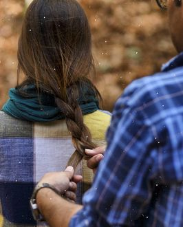 Фото Парень ухаживает за девушкой, заплетая ей косу