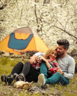 Фото Влюбленные сидят на земле недалеко от палатки
