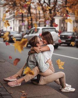 Фото Парень и девушка в объятиях сидят у дороги под листопадом
