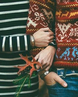 Фото Девушка с осенним листиком и хвойной веточкой держит парня за руку