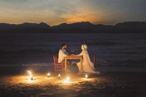 Фото Свадебная пара сидит за столиком на фоне моря. Фотограф Durdali Dalgin
