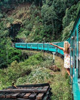 Фото Девушка стоит в дверях тамбура и смотрит в конец поезда