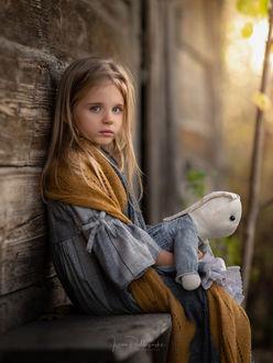 Фото Девочка с игрушкой в руках сидит на лавочке у дощатой стены дома, фотограф Iwona Podlasinska