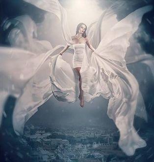 Фото Девушка в белом платье парит над городом