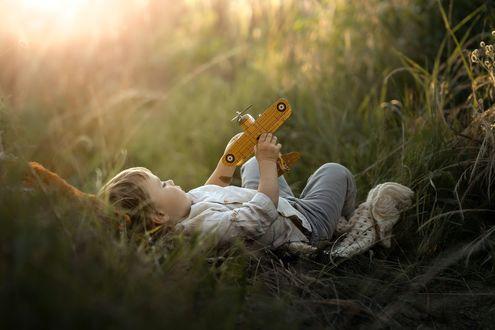 Фото Мальчик с игрушечным самолетиком лежит в траве, фотограф Iwona Podlasinska