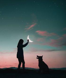 Фото Собака смотрит на девочку с полумесяцем в руке