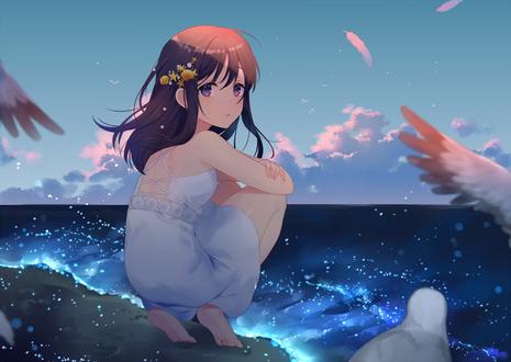 Фото Девочка с цветочками в волосах сидит у моря