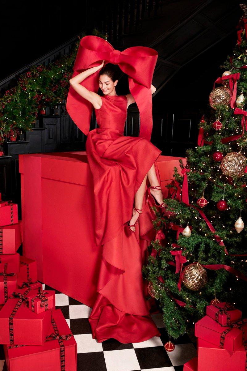 Фото Модель Лили Олдридж в красном сидит на подарочной коробке перед елкой