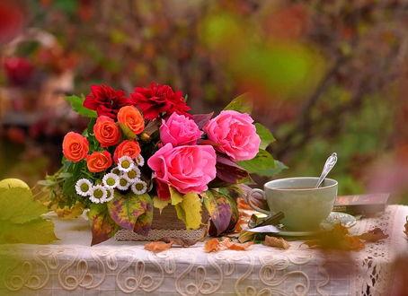 Фото Букет, состоящий из разных цветов, в осенних листьях на столе с чашечкой чая