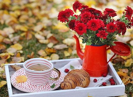 Фото Букет красных цветов на подносе рядом с кружкой и булочкой