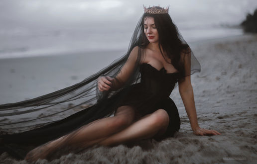 Фото Девушка в черном плате, с короной на голове сидит на песке. Фотограф Budrikayte Viktoria