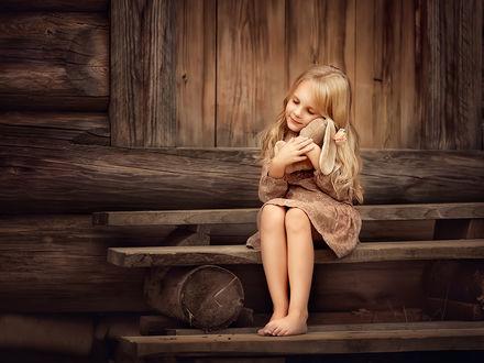 Фото Милая девочка с игрушечным зайчиком сидит на ступеньках. Фотограф Елена Михайлова