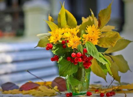Фото Букет, составленный из цветов, ягод и осенних листьев, на столе в вазе