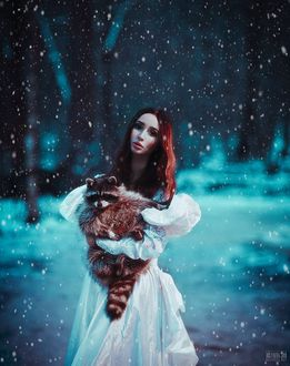 Фото Девушка с енотом в руках стоит под снегопадом. Фотограф Светлана Беляева