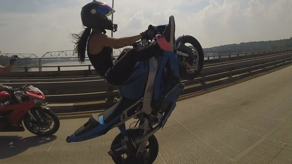 Фото Девушка показывает трюк на мотоцикле