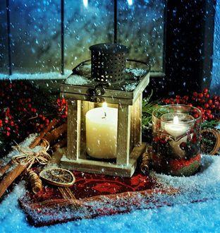 Фото Горящие свечи, рябина, палочки корицы под снегопадом