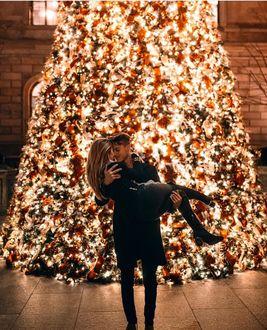 Фото Парень держит девушку на фоне новогодней елки