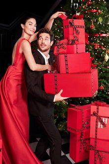 Фото Модель Лили Олдридж в красном платье обнимает парня с коробками подарков