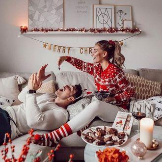 Фото Девушка кормит лежащего парня рождественскими угощениями