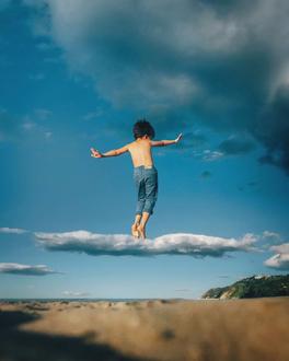 Фото Мальчик стоит на облаке