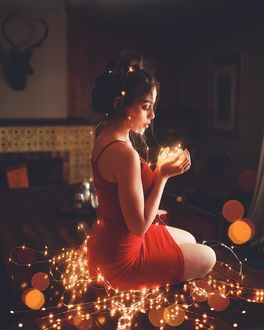 Фото Девушка с гирляндой сидит на полу, by luiz claudio