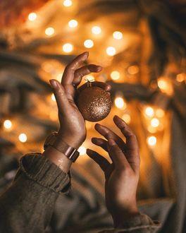 Фото В руке девушки новогодний шар на фоне боке, by anamarkovych