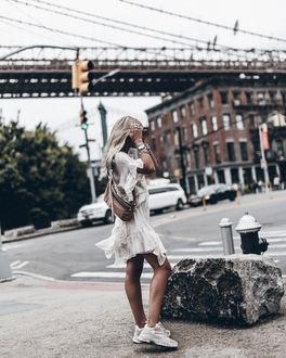 Фото Девушка в легком платье, в кроссовках, стоит на улице города, by mikuta. nu