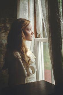 Фото Грустная девушка смотрит в окно. Фотограф TJ Drysdale
