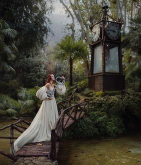 Фото Девушка в длинном белом платье с большим ключом в руке стоит на мостике. Фотограф Irina Dzhul