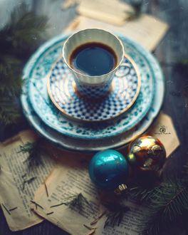 Фото Чашка кофе на блюдце с тарелками и елочные игрушки на столе, by mironovatanyahoo