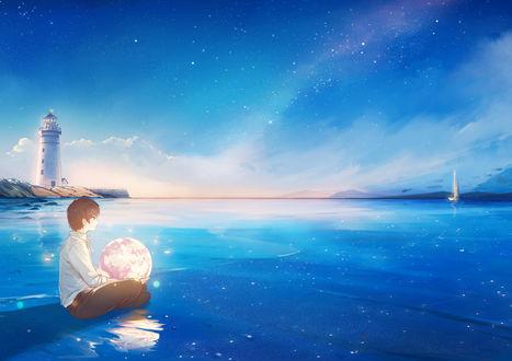 Фото Парень с луной в руках сидит на морском берегу во время прилива