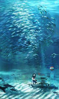 Фото Девочка сидит на лавочке под водой с рыбами над головой