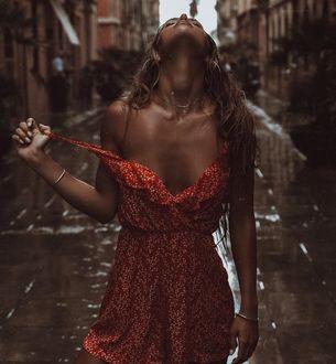 Фото Загорелая девушка в красном сарафане с оголенным плечом стоит, запрокинув голову назад, под дождем на городской улице