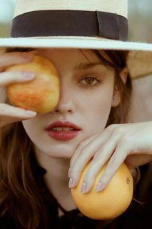 Фото Портрет девушки в шляпе с апельсинами в руках