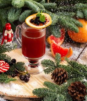Фото Глинтвейн с лимоном и ягодами среди хвои и шишек на деревянном срубе