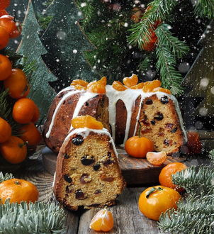 Фото Кусочки кекса с дольками мандарина среди снега и хвои
